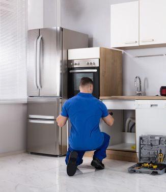 kodinkoneiden asennus Espoossa, asentaja asentaa keittiötä
